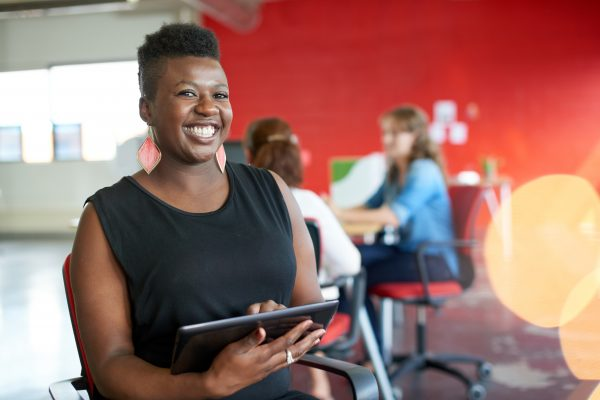 Casual portrait of an african american business woman using technology in a bright and sunny startup with the team in the background